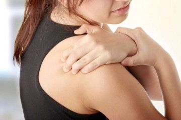 Дівчина тримається за плече