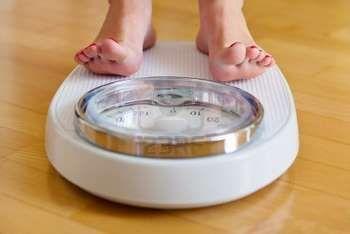 Дівчина стоїть на вагах