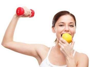 Дівчина їсть яблуко і тримає гантелю
