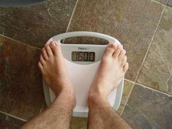 Чоловік стоїть на підлогових вагах