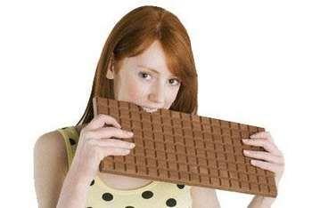 Дівчина кусає дуже велику плитку шоколаду
